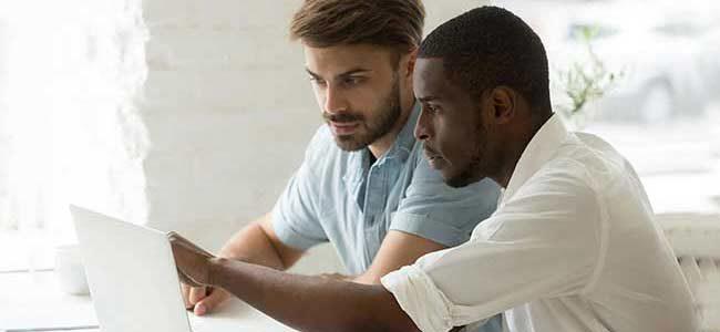 two man looking at computer